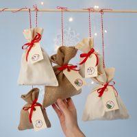 Un calendrier de l'Avent fait avec des sacs en tissu et des numéros autocollants placés sur des étiquettes cadeaux