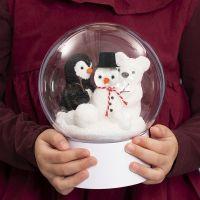 Un boule transparente sur un socle avec un bonhomme de neige, un pingouin et un ours polaire à l'intérieur