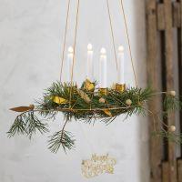 Une couronne de l'Avent à suspendre avec des bougeoirs en fil bonsaï et  des décorations en papier imitation cuir