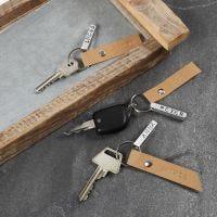 Un porte-clé avec une gourmette gravée d'un prénom et une étiquette en papier imitation cuir