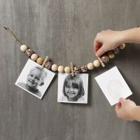 Photos sur un morceau de ficelle naturelle décorée avec des perles, des pinces à linge et des sequins
