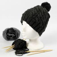 Un bonnet tricoté avec un motif torsadé et un pompon