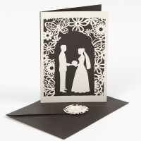 A wedding invitation with a punched-out wedding design and laced card