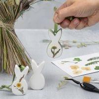 Des décorations de Pâques en porcelaine à suspendre, décorées de fleurs séchées