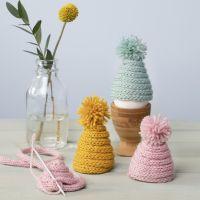 Un chauffe-oeuf tricoté fait avec un tube de laine et un pompon