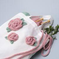 Un sac à provisions décoré de roses faites à partir d'un tube tricotés