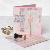 Une carte de voeux décorée avec du papier fait main, des motifs imprimés, de la cire et un sceau
