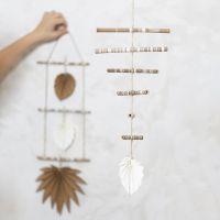 Un mobile fait avec des bâtons de bambou décorés et du papier imitation cuir