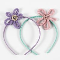 Des serre-têtes décorés de fleurs en tube tricoté