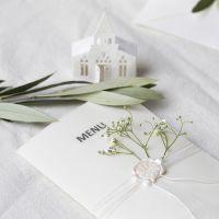 Une carte de menu dans des tons blanc cassé avec une église perforée et du papier vélin
