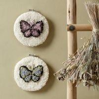 Des papillons brodés au poinçon à broderie dans un cadre à broder