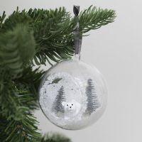 Une boule de Noël avec un orifice sur la face antérieure, décorée de neige artificielle et de mini figurines