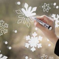 Une fenêtre décorée avec des flocons de neige faits avec des feutres à craie